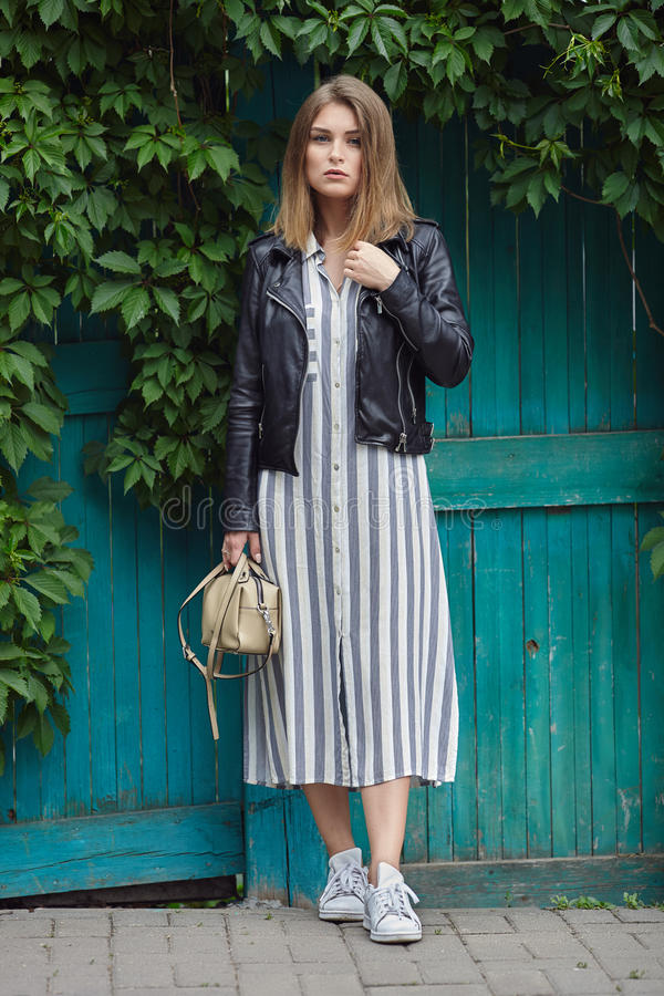 Young beautiful girl in stylish streetwear black leather jacket long striped dress white sneakers and with a fashionable bag posin. G against turquoise wooden royalty free stock photography
