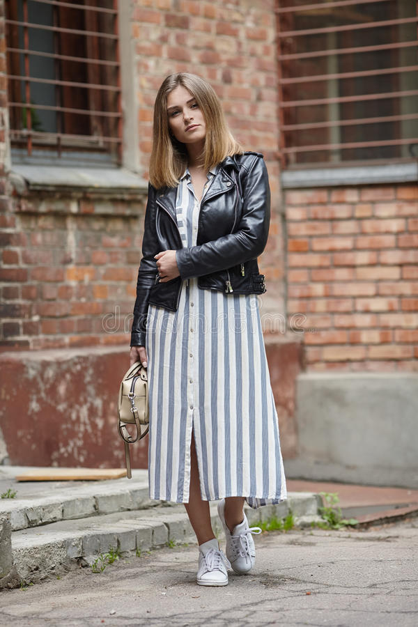 Young beautiful girl in stylish streetwear black leather jacket long striped dress white sneakers and with a fashionable bag posin. G against brick wall royalty free stock photo