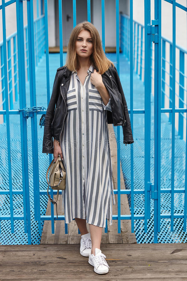 Young beautiful girl in stylish streetwear black leather jacket long striped dress white sneakers and with a fashionable bag posin. G against blue painted metal royalty free stock images