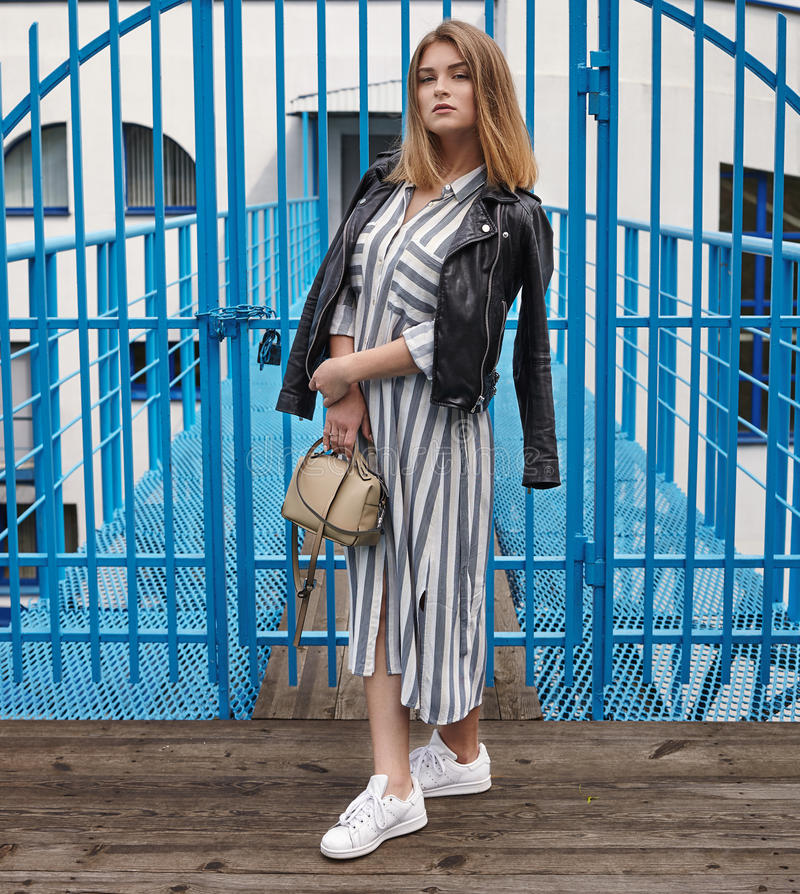 Young beautiful girl in stylish streetwear black leather jacket long striped dress white sneakers and with a fashionable bag posin. G against blue painted metal stock images