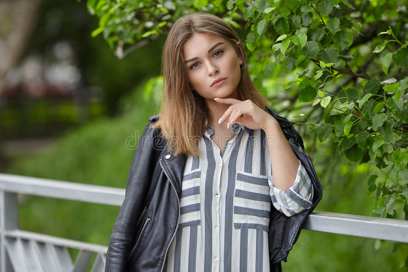 Young beautiful girl in stylish streetwear black leather jacket long striped dress white sneakers and with a fashionable bag posin. G on bridge in summer city stock photo