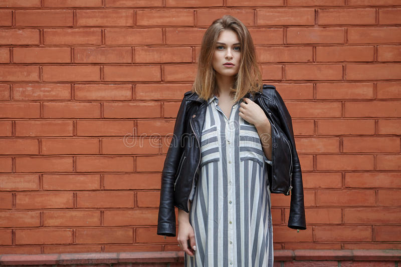 Young beautiful girl in stylish streetwear black leather jacket long striped dress white sneakers and with a fashionable bag posin. G against terracotta brick stock photo