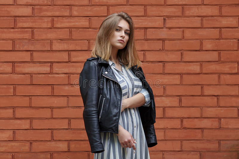 Young beautiful girl in stylish streetwear black leather jacket long striped dress white sneakers and with a fashionable bag posin. G against terracotta brick royalty free stock photo