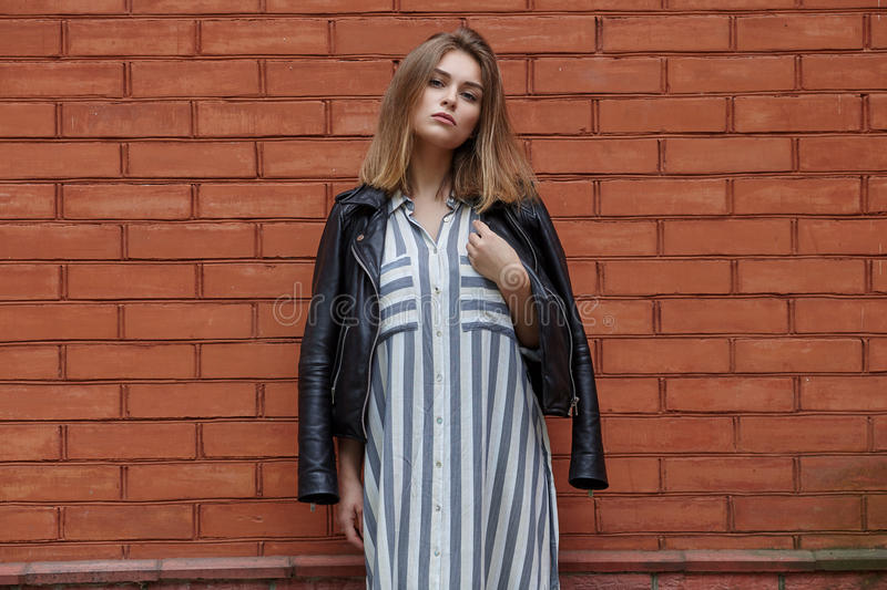 Young beautiful girl in stylish streetwear black leather jacket long striped dress white sneakers and with a fashionable bag posin. G against terracotta brick royalty free stock photography