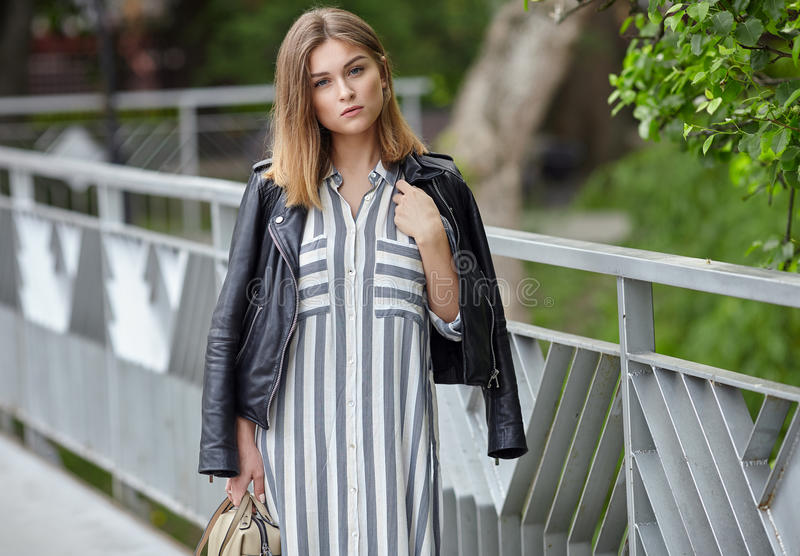 Young beautiful girl in stylish streetwear black leather jacket long striped dress white sneakers and with a fashionable bag posin. G on bridge in summer city royalty free stock images