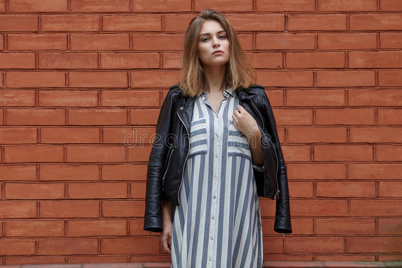 Young beautiful girl in stylish streetwear black leather jacket long striped dress white sneakers and with a fashionable bag posin. G against terracotta brick stock photography