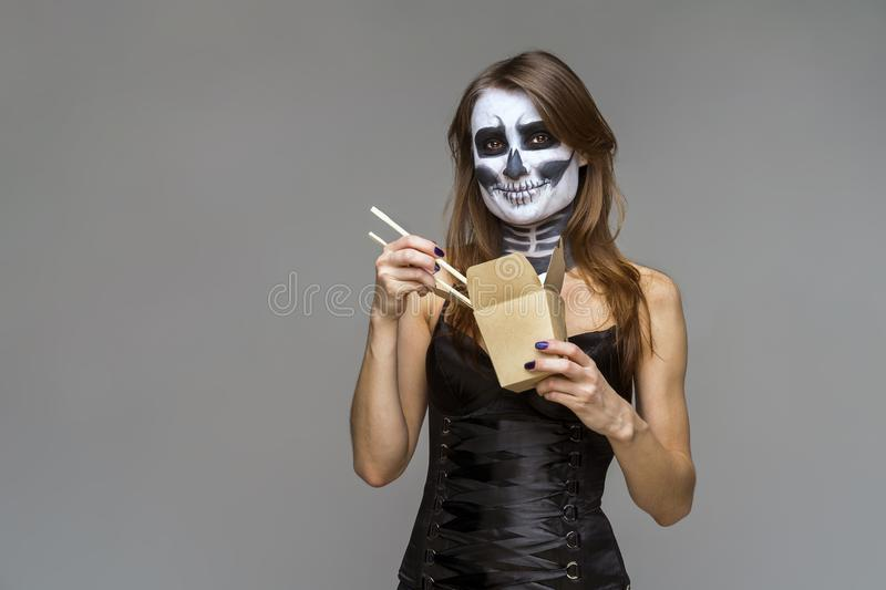 Young beautiful girl with a sugar skull make up, holds in her hand a paper box for instant noodles and chopsticks. Halloween face stock photo