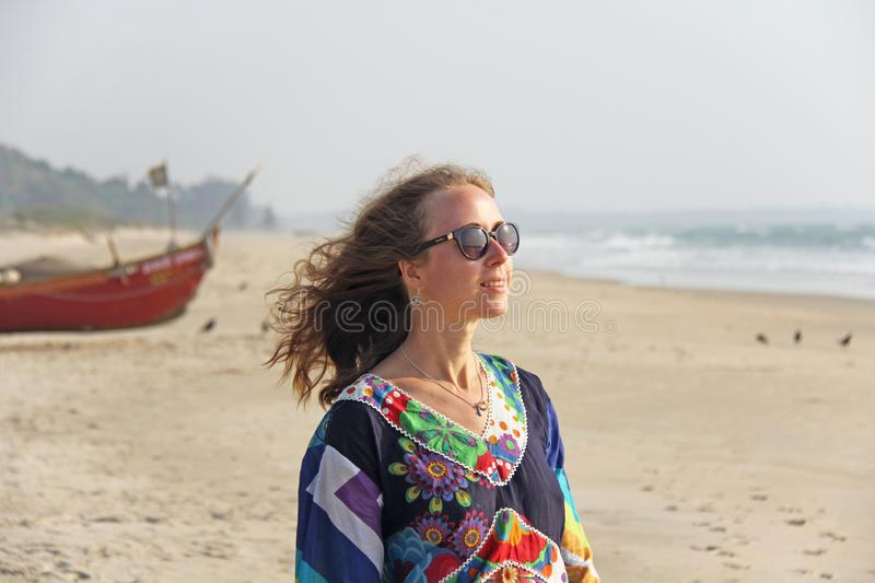 Young and beautiful girl in sunglasses, with blond hair, smiling at the beach and looking at the sea. A girl in a bright summer royalty free stock image