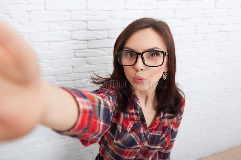 Young Beautiful Girl Taking Selfie Picture With Duck Face Lips Smart Phone Photo Camera. Over White Brick Wall royalty free stock photography