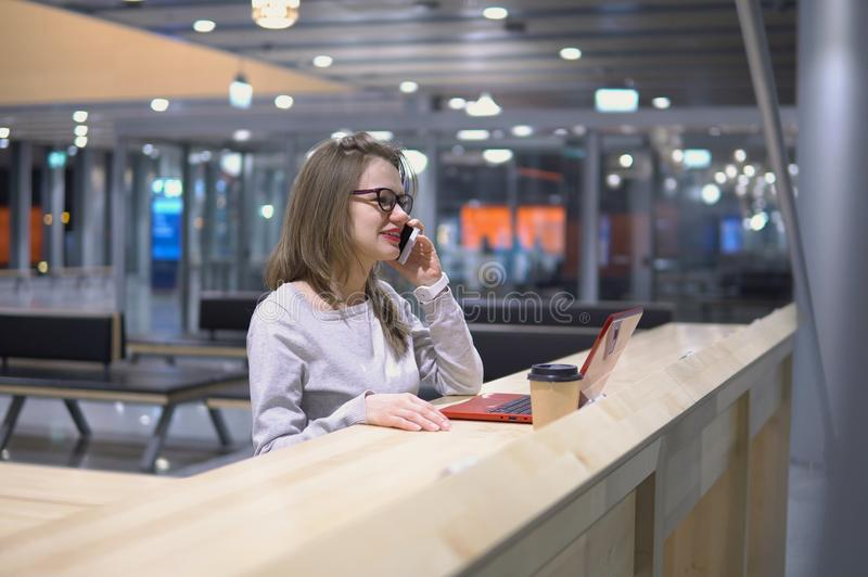 Young, beautiful girl talking on the phone standing at a table with a laptop and a cup of coffee at the airport royalty free stock photos