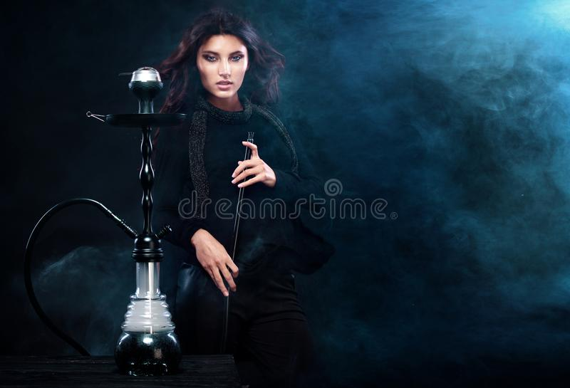 Young, beautiful woman in the night club or bar smoke a hookah. The pleasure of smoking. smoke. Young, beautiful girl in trendy club clothes and perfect make up stock images