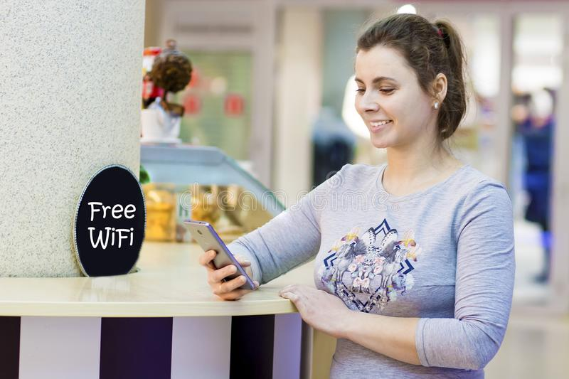 Young beautiful girl uses smartphone in free Wi Fi zone in shopping mall cafe. Attractive woman Wifi zone. Free wi-fi concept. royalty free stock photography