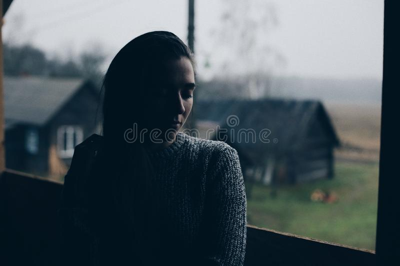 Young beautiful girl in the village. Model on background of a wooden house in the village. Dark light. royalty free stock image