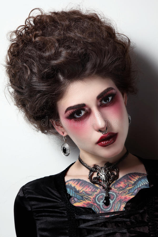 Young beautiful girl with vintage hairdo and gothic stock image