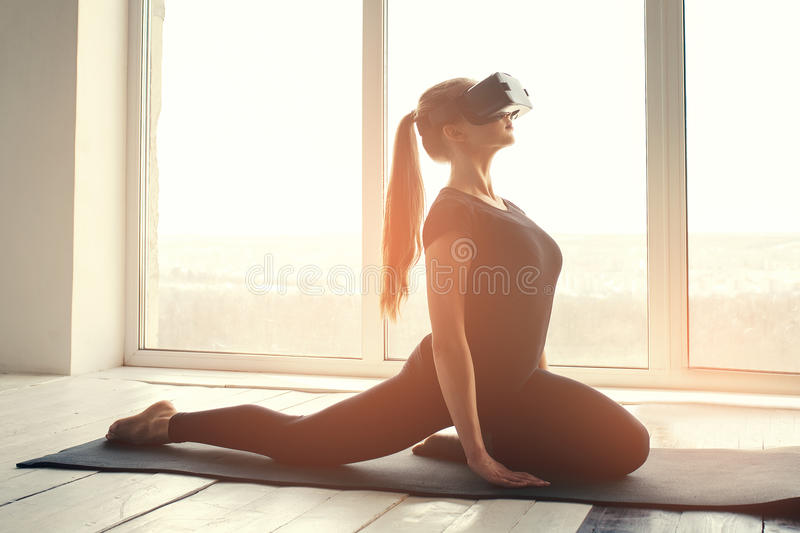 A young beautiful girl in virtual reality glasses makes yoga and aerobics remotely. Future technology concept. Modern. A young beautiful girl in virtual reality stock photos