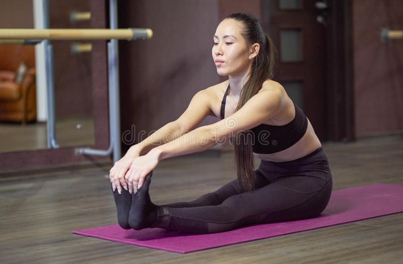 Young beautiful girl wearing fashion sports wear doing exercise on mat at loft gym, top view royalty free stock photo