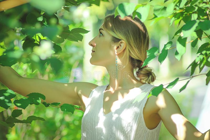 Young beautiful girl in a white dress close-up on the background of green bushes with flowering jasmine royalty free stock photo