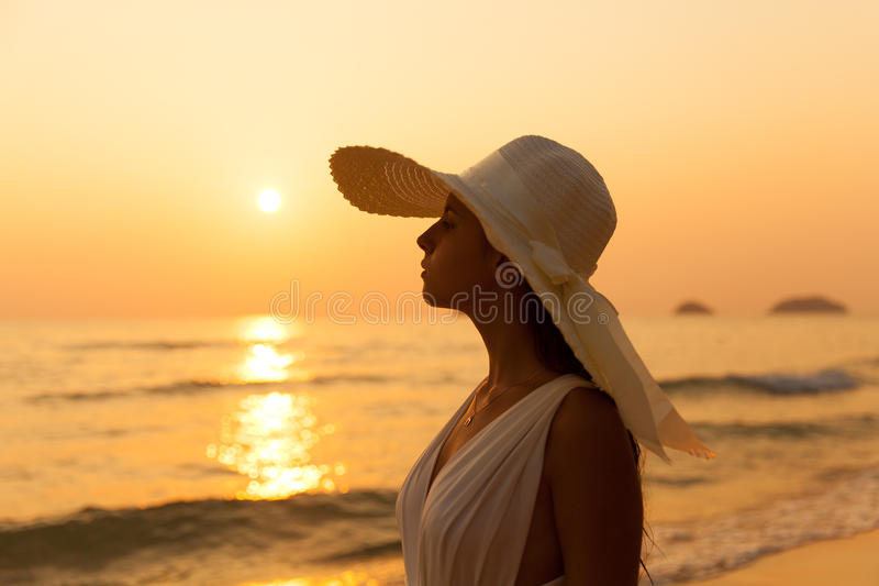 Young beautiful girl in a white dress and straw hat on a tropical beach at sunset. Summer vacation concept. stock photography