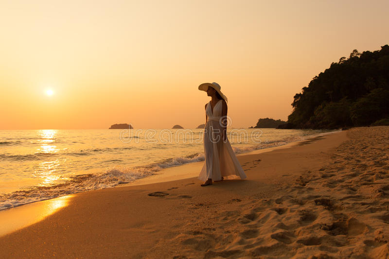 Young beautiful girl in a white dress and straw hat on a tropical beach at sunset. Summer vacation concept. royalty free stock images