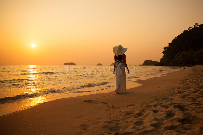 Young beautiful girl in a white dress and straw hat on a tropical beach at sunset. Summer vacation concept. stock image