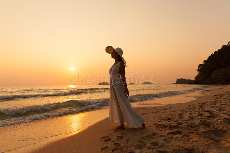 Young beautiful girl in a white dress and straw hat on a tropical beach at sunset. Summer vacation concept. stock photo