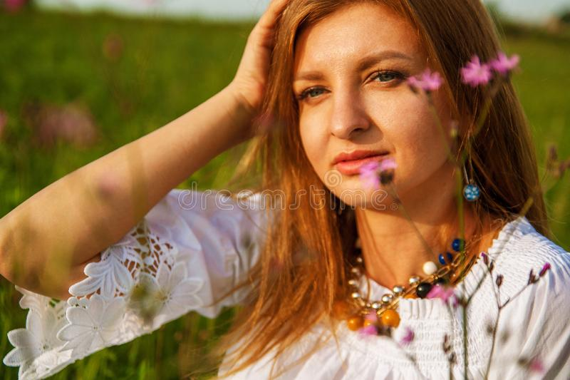 Young beautiful blonde woman smilling with flowers in nature in the summer. stock photography