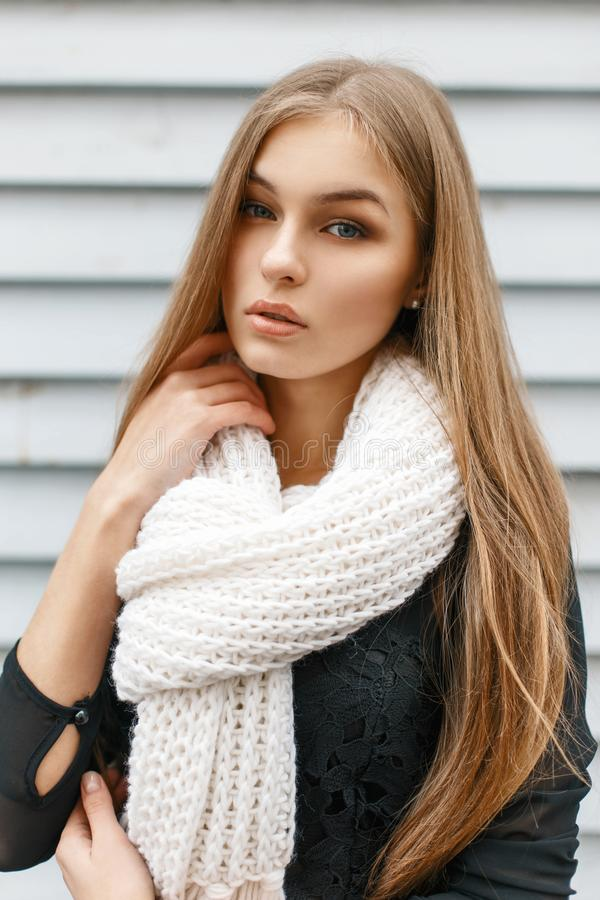 Young beautiful girl in a white knit scarf and a black dress on. A background of a wooden wall royalty free stock image