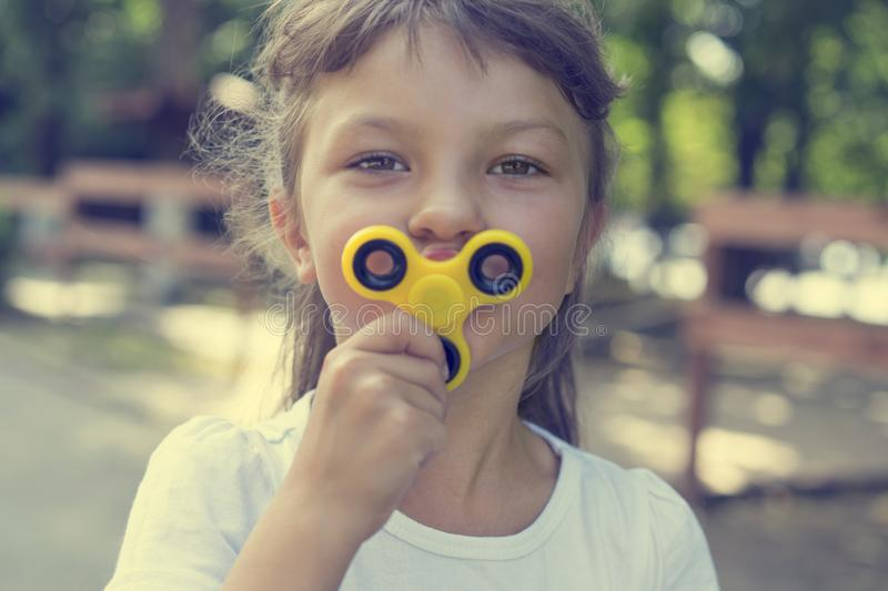 A young beautiful girl in a white T-shirt attached to the face a yellow spinner on the street royalty free stock photo