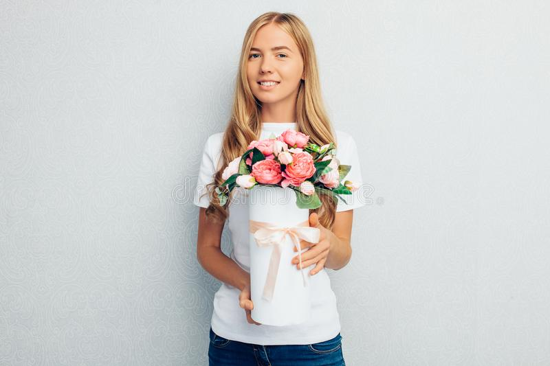 Young beautiful girl in white t-shirt holding bouquet of flowers standing on grey background stock photos