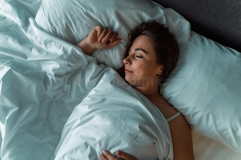 Young beautiful girl or woman sleeping alone in big bed at night, top view. Toned stock photography