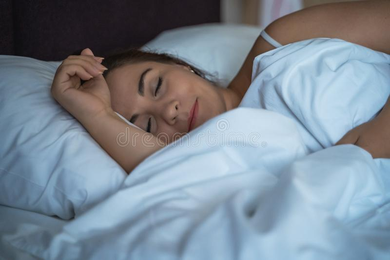 Young beautiful girl or woman sleeping alone in big bed at night.  royalty free stock photo