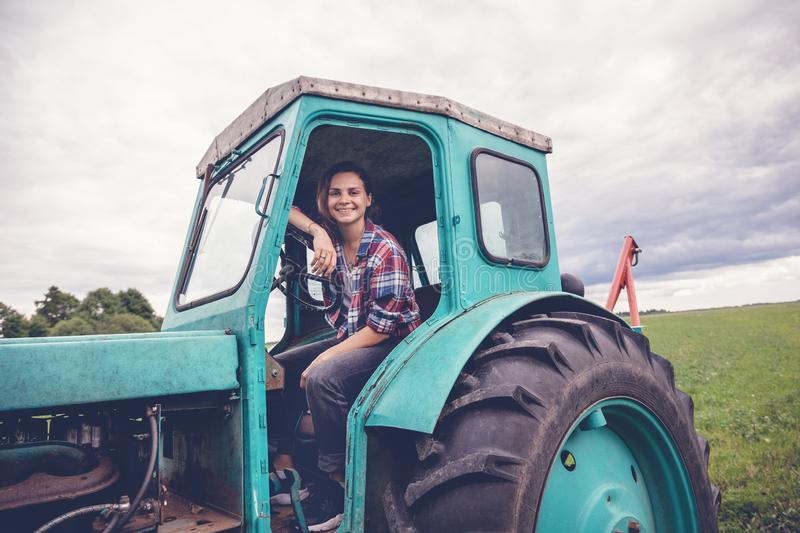 Young beautiful girl working on tractor in the field, unusual work for women, gender equality concept royalty free stock photo