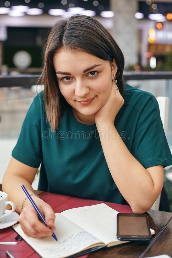 Young beautiful girl writes something in her notebook while sitting in the office stock photo