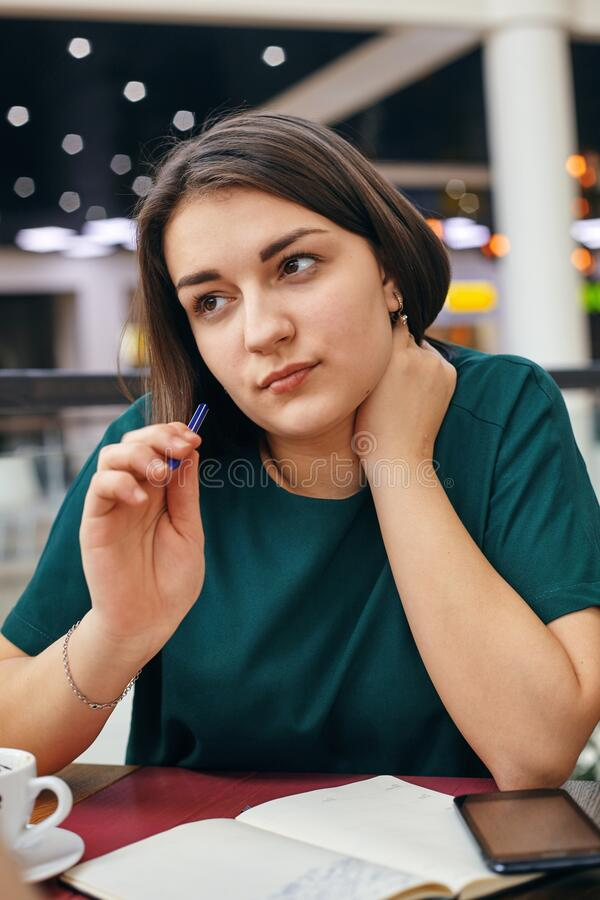 Young beautiful girl writes something in her notebook while sitting in the office stock image