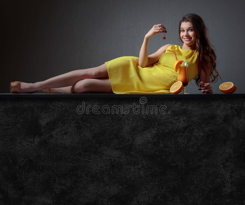 Young beautiful girl in a yellow dress with cocktail Tequila Sun stock images