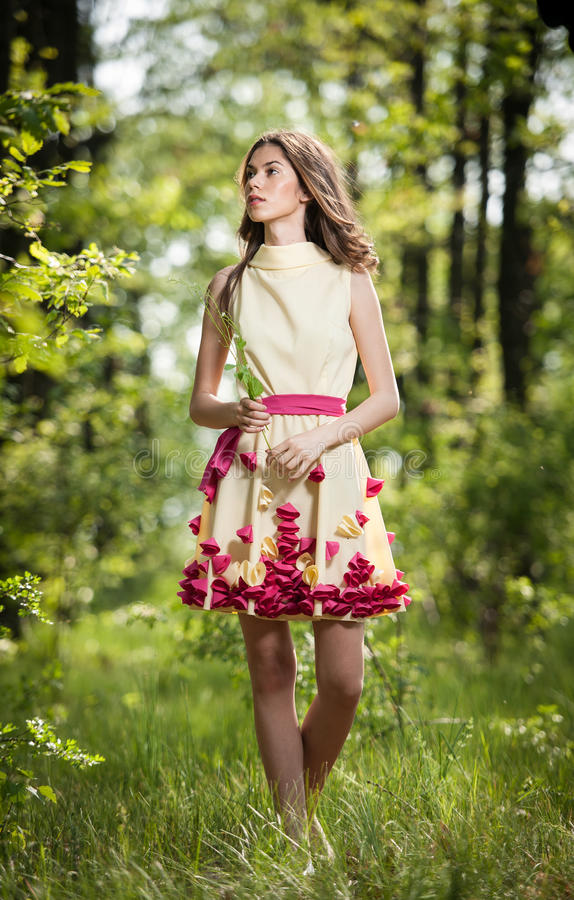 Young beautiful girl in a yellow dress in the woods. Portrait of romantic woman in fairy forest. Stunning fashionable teenager stock images