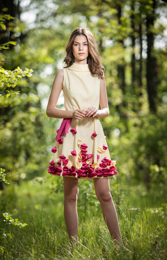 Young beautiful girl in a yellow dress in the woods. Portrait of romantic woman in fairy forest. Stunning fashionable teenager. Young beautiful girl in a yellow royalty free stock photos