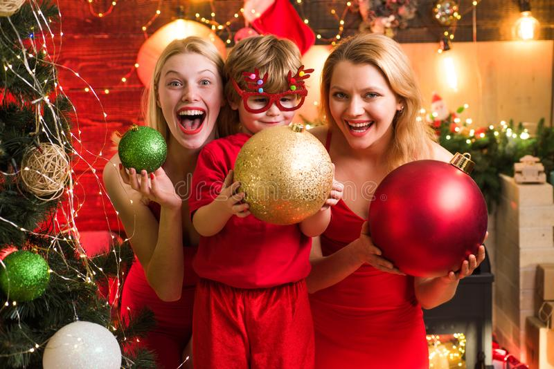 Young beautiful Girls and small little kid by the Christmas tree.Two Christmas girls are wearing red dresses on the. Christmas tree background stock images