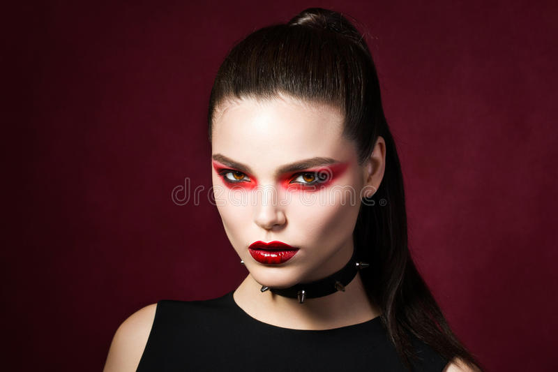 Young beautiful gothic woman with white skin and red lips royalty free stock images