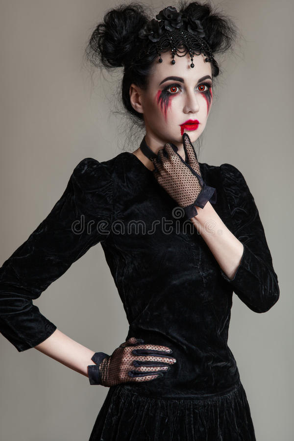 Young beautiful gothic woman with white skin and red lips. Halloween royalty free stock photography