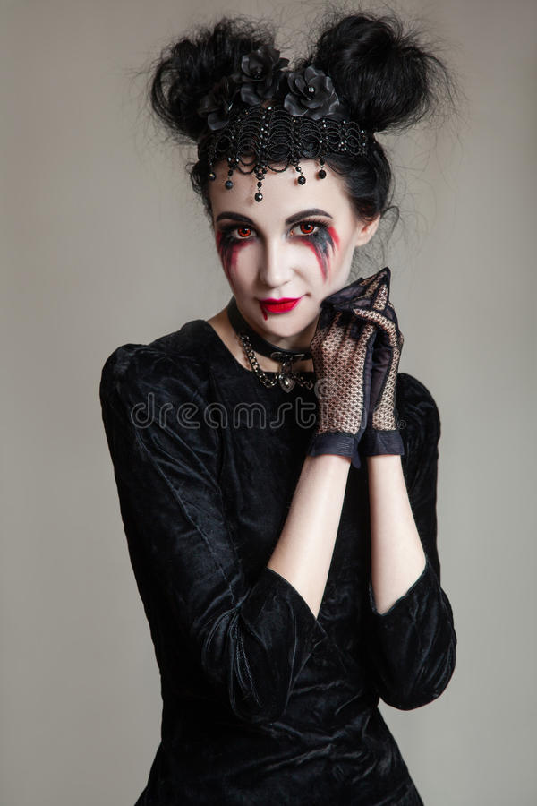 Young beautiful gothic woman with white skin and red lips. Halloween stock photography