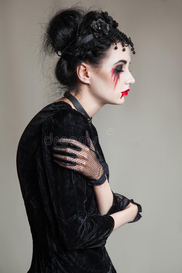 Young beautiful gothic woman with white skin and red lips. Halloween stock photos