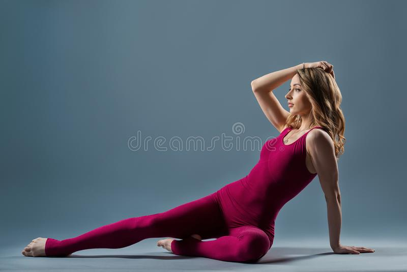 Young beautiful gymnast woman in a jumpsuit shows gymnastic poses and exercises. Sport is a flexible, healthy body. Fit sporty. Girl is stretching royalty free stock photo