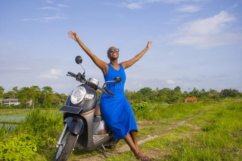 Young beautiful and happy african american black woman posing co. Ol on scooter motorbike at green field tropical landscape in adventure trip and summer holidays royalty free stock photo