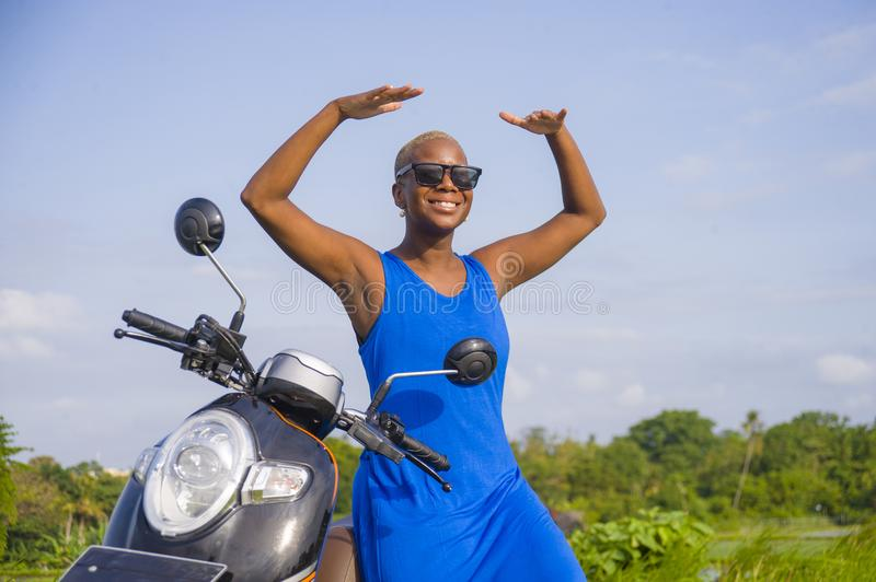 Young beautiful and happy african american black woman posing cool on scooter motorbike at green field tropical landscape in adven. Ture trip and summer holidays stock image
