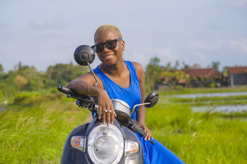 Young beautiful and happy african american black woman posing cool on scooter motorbike at green field tropical landscape in adven. Ture trip and summer holidays stock photo