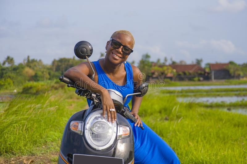 Young beautiful and happy african american black woman posing cool on scooter motorbike at green field tropical landscape in adven. Ture trip and summer holidays royalty free stock image