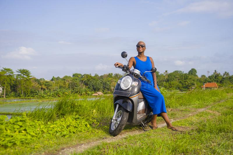 Young beautiful and happy african american black woman posing cool on scooter motorbike at green field tropical landscape in adven. Ture trip and summer holidays royalty free stock photography