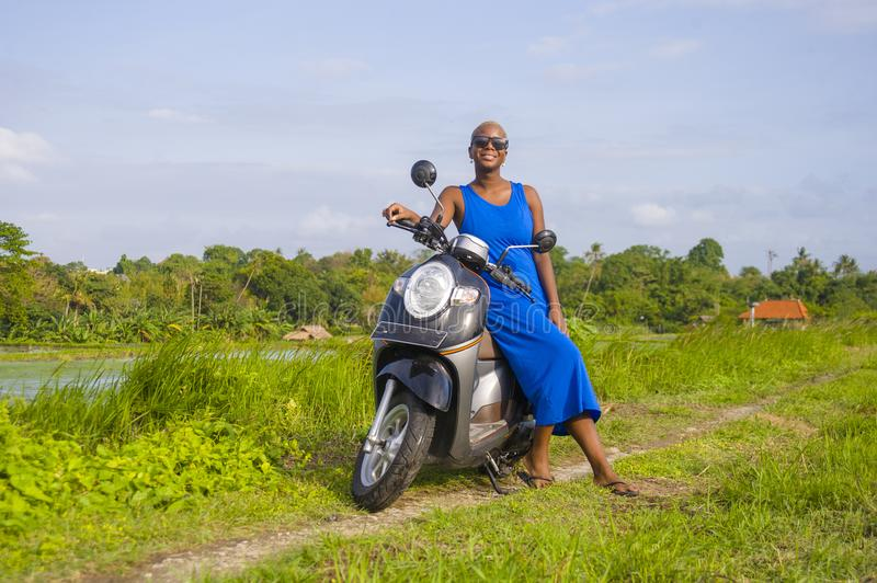 Young beautiful and happy african american black woman posing cool on scooter motorbike at green field tropical landscape. In adventure trip and summer holidays royalty free stock photos