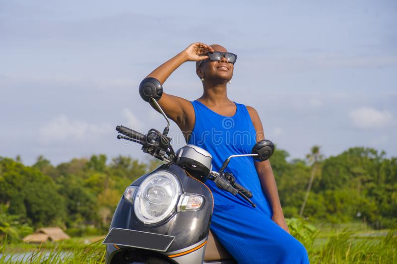 Young beautiful and happy african american black woman posing cool on scooter motorbike at green field tropical landscape. In adventure trip and summer holidays royalty free stock image